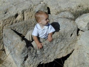 Ancient Israeli stone manger with a little tourist child sitting in it