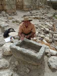 Ancient Israeli stone manger with tourist next to it.